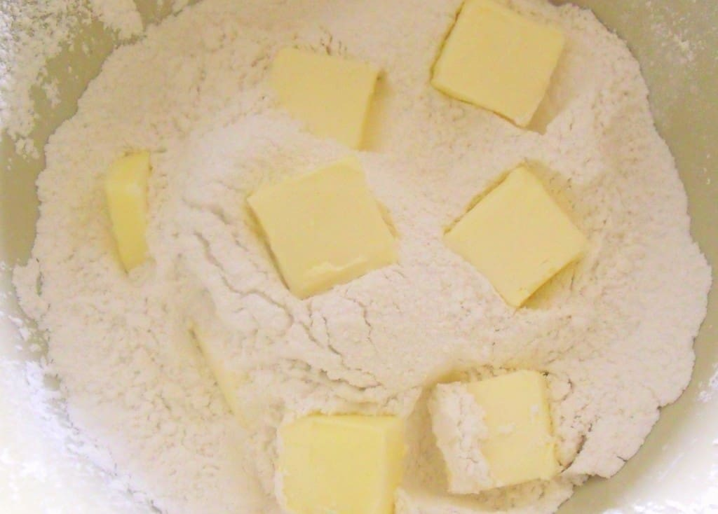 Knobs of butter on top of a bowl of flour for soda bread