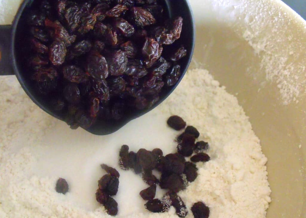 Raisins being dropped into a bowl of flour for soda bread