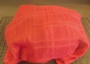 A red tea towel or dish cloth covering a loaf of Irish soda bread