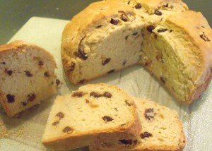 A round loaf of Irish raisin soda bread with two slices cut from one quarter
