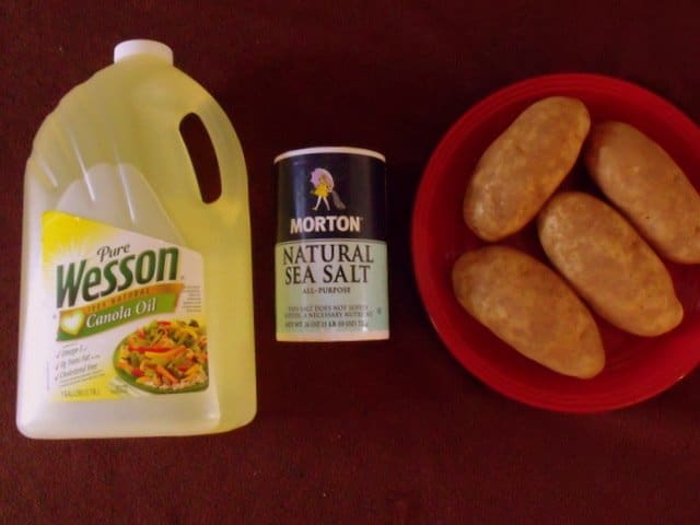A large bottle of cooking oil, natural sea salt and four russet potatoes