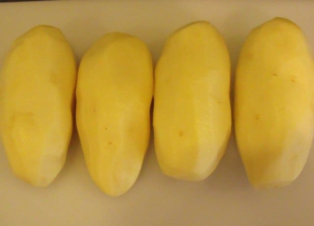 Four peeled russet potatoes on a chopping board