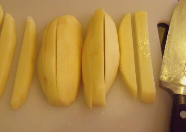 Potatoes on a chopping board beside a knife and cut into lengths for making french fries