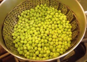 Peas in a metal steamer inside a saucepan