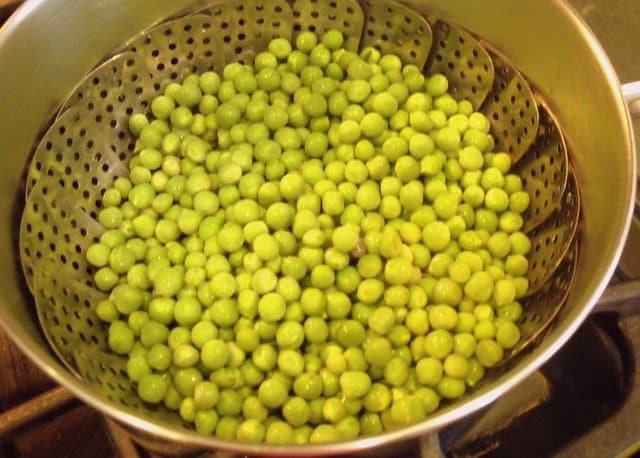 Peas in a metal steamer inside a saucepan