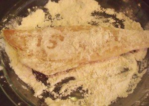 A piece of cod in a plate of seasoned flour