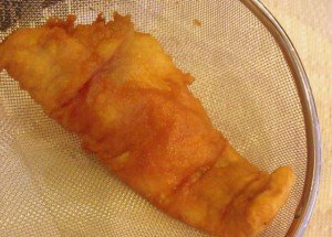 A piece of beer battered fish in a strainer over paper towel