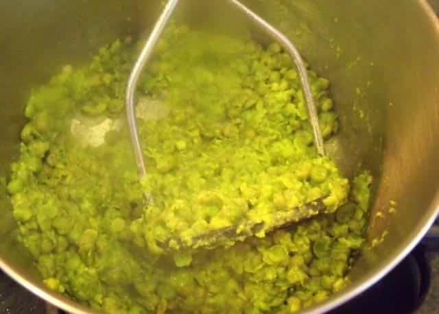 Using a masher to mush peas for mushy peas