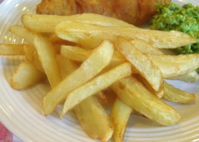 Irish style french fries or chips on a white plate beside fried fish and mushy peas