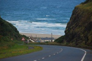Approaching Downhill beach by steep roadway with house beside the strand