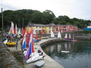 The pier beside a yellow shop and red hotel in Glandore County Cork