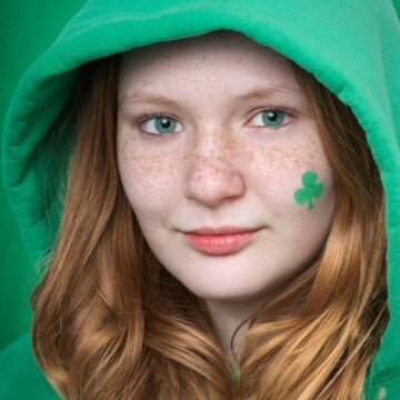 A red haired girl with green eyes and a shamrock painted on her cheek
