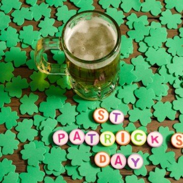 A tankard of beer standing in shamrocks beside text buttons
