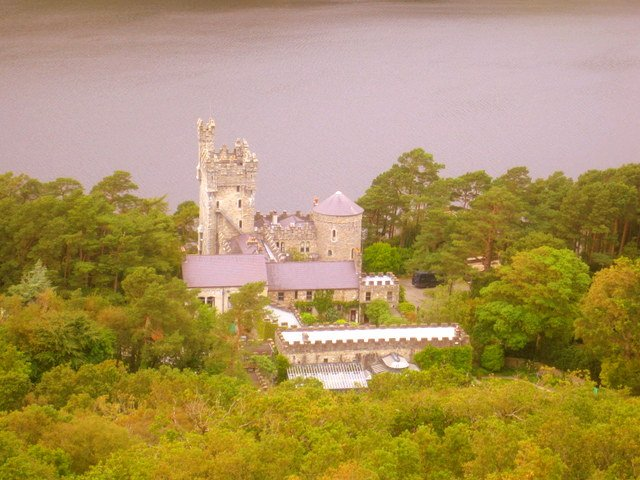 A castle surrounded by trees and a lake