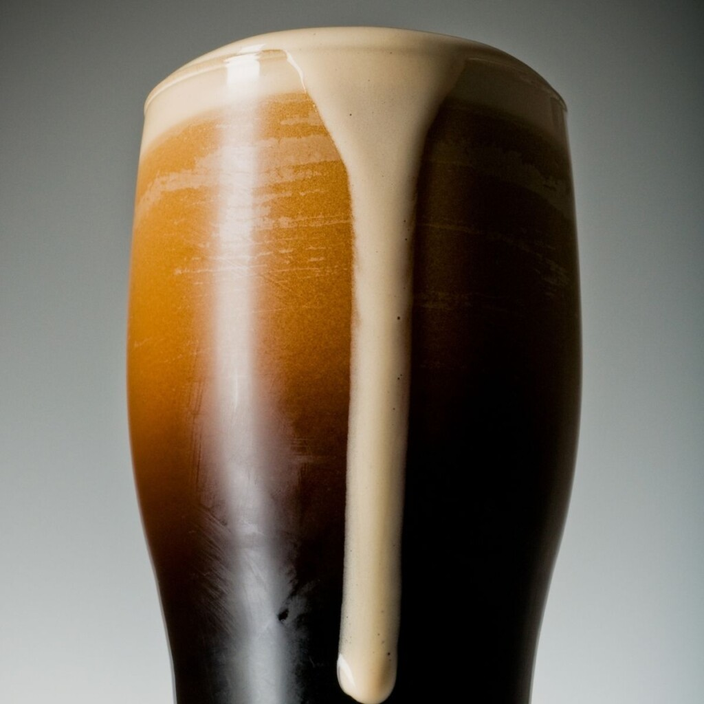 Black porter in a glass with foam streaming down the side of the glass