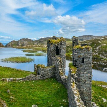 Stone castle towers in a green field beside an inlet of the ocean