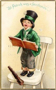 A green jacketed boy on a chair holding a song book