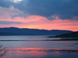 The sun sets casting red glowing shadows over the Swilly River in County Donegal