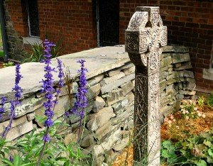 A stone wall with a Celtic Cross memorial stone in New York