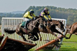 Two horses jump over a breaking fence in a horse race