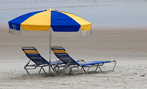Yellow and blue beach umbrella over two sun loungers
