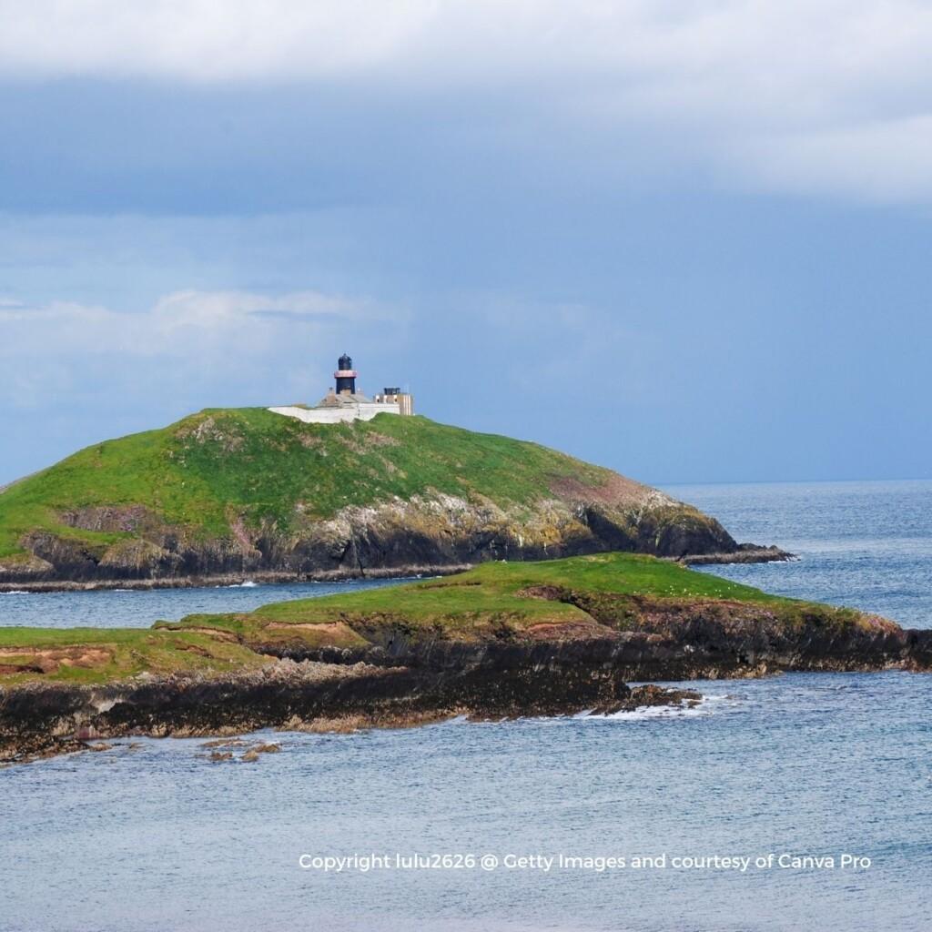 A black lighthouse on a green island off a rocky coast