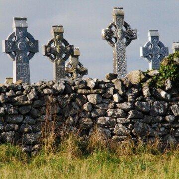 Celtic crosses behind a stone wall beneath a grey sky