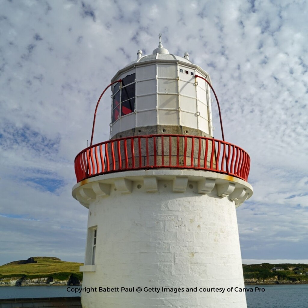 A white lighthouse tower with a red railing around the upper beacon