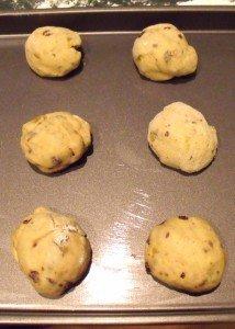 Dough balls on a baking tray for hot cross buns