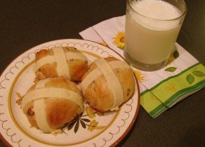 A glass of milk with three hot cross buns on a plate