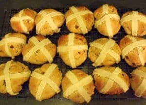 15 hot cross buns cooling on a wire rack before serving