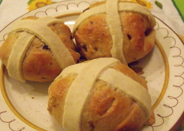 Three hot cross buns with pastry crosses on a plate