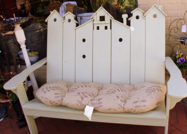 A wooden bench with bird house carvings on the back