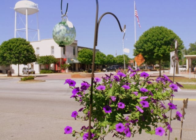A water tower with a hanging flower basket in the foreground