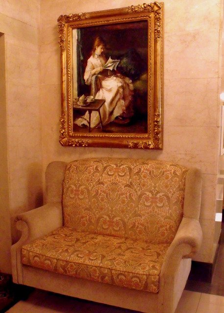 Brocade sofa beneath an oil painting of a woman in a long gown reading a book