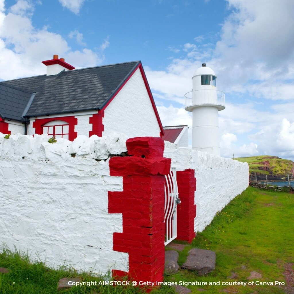 Cottage behind a red and white wall with a lighthouse in the distance