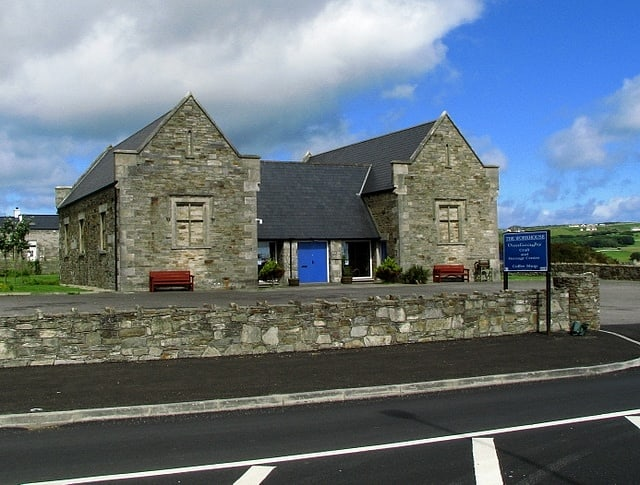 STone building with a wall beside a road