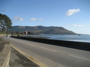 Road by the coast in County Down showing the mountains of Mourne