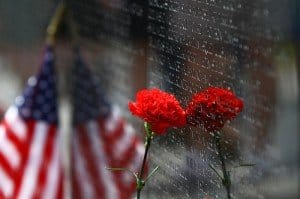 A carnation and American flag reflect on the wall of the Vietnam War Memorial in Washingon DC