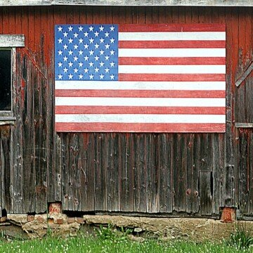 An American flag wooden art piece hanging on the side of an old wooden structure