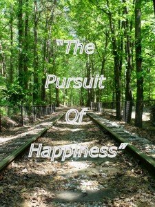 A railroad track with the slogan the pursuit of happiness