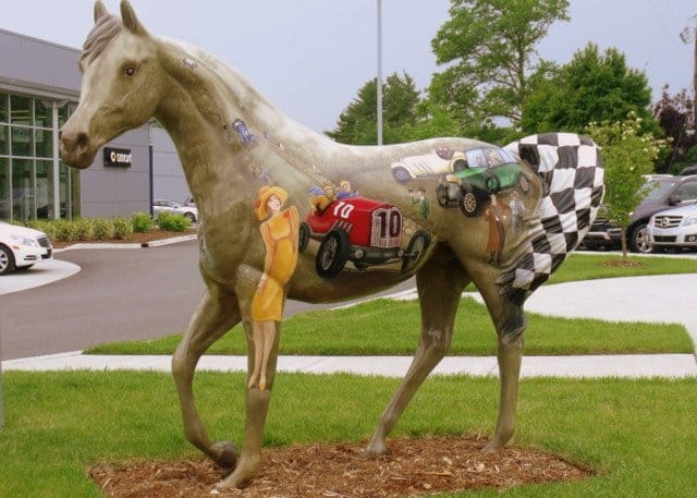 A horse statue decorated with vintage autos and cars