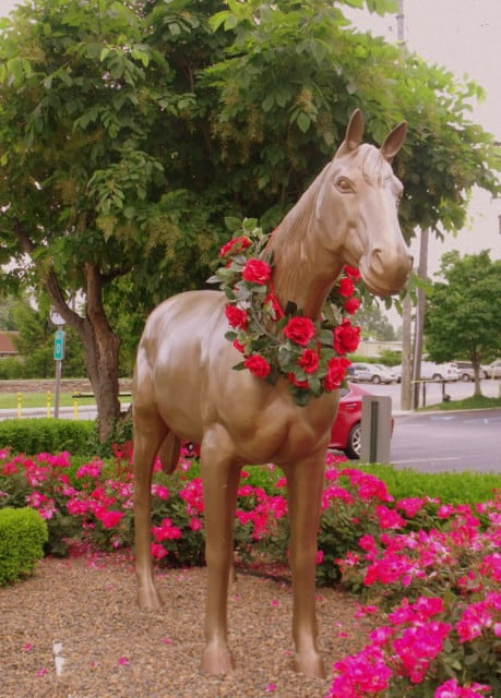A horse statue in front of a flower bed