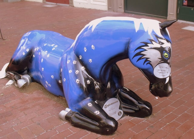 A horse statue in blue and black lying on a street