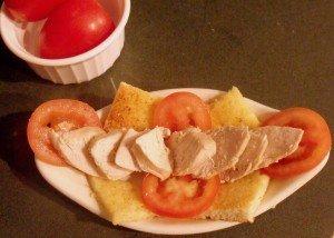 Lining cooked turkey on an open face bread sandwich for a Kentucky Hot Brown Sandwich