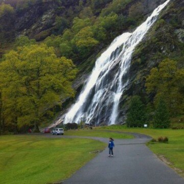 A tall waterfall cascading down a hill side with a road leading up to it
