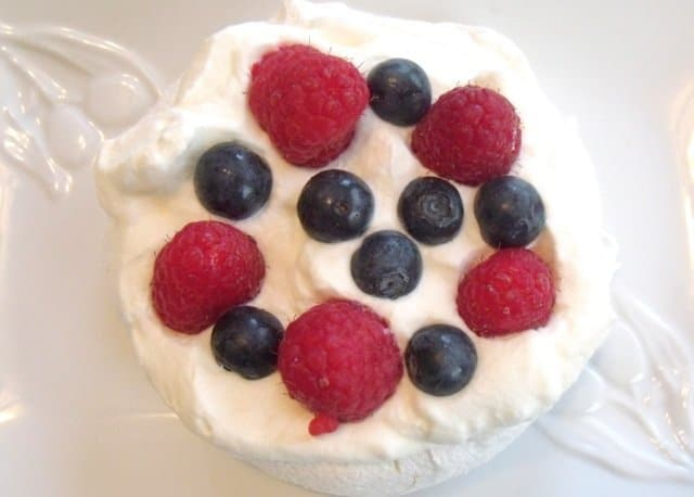 Aerial view of a mini pavlova decorated with cream and berries.