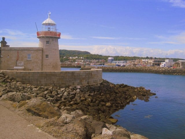 A round stone wall on a pier beside a lighthouse