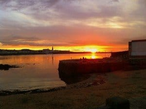 Orange glowing sky as the sun sets over the water in Sandycove