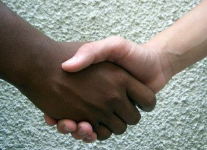 Two hands clasped in a handshake one black, one white